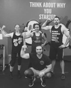 A group of 4 gym members poses for a flexing photo.