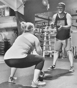 A trainer instructs and encourages proper form as a member completes a kettlebell squat.