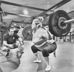 A member practices a squat under instruction from a trainer.