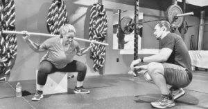 A trainer practices proper squat technique and form with a member.