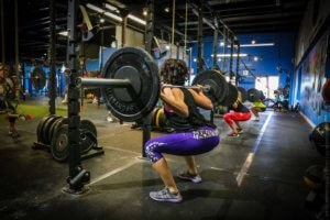 A photo of a woman squatting with barbell at Elite Edge.