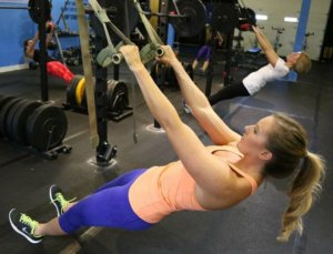 A photo of a woman utilizing TRX.